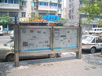 Media of China - A current issue of Renmin Ribao posted on a newspaper display board in Hangzhou