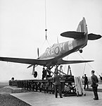 Hawker Sea Hurricane Mk I of the Merchant Ship Fighter Unit being lowered onto the training catapult at Speke, Liverpool, for a training launch, March 1942. CH15390.jpg