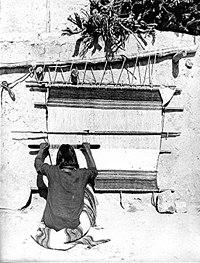 ผู้ชายชาวโฮปีคนหนึ่งกำลังทอผ้าด้วยเครื่องทอพื้นเมืองใน