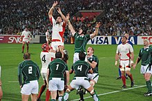 Two rows of opposing players, green to the fore, white behind, each aiding a jumping player from their team by lifting him towards an off-picture ball travelling overhead