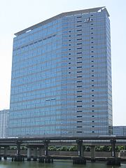 "A modern multistorey building in blue and grey colour, with Japan Airlines' ""JAL"" logo on the top right, blue sky on the background, and a highway bridge in the foreground"
