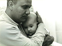 Chinmoy embracing a baby