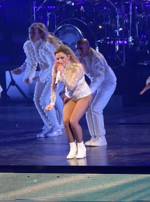Gaga flanked by dancers perform on stage, wearing white garments.