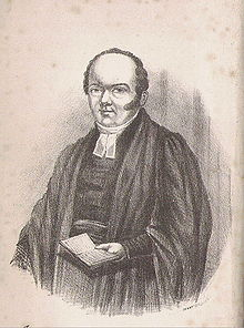 A balding clergyman in gown and clerical garb, holding an open book in his left hand