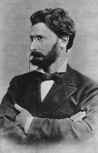 Foto in bianco e nero di un magro con lo sguardo severo, ovviamente occhialini sul naso barba e baffi volto allungato, braccia conserte
