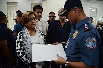 Leila de Lima - Senator Leila De Lima listens to a PNP-CIDG officer who served the warrant for her arrest at the Senate grounds in Pasay. February 24, 2017.