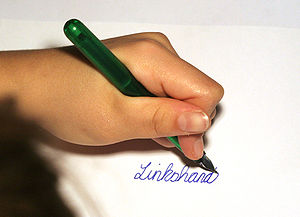 Left hand writing the German word