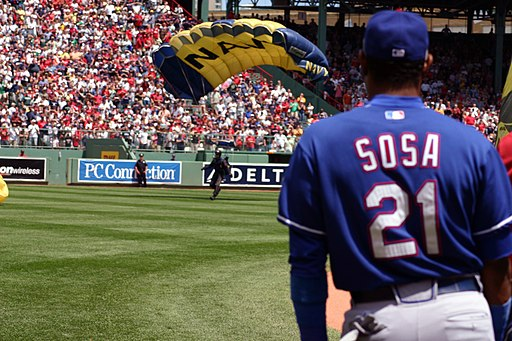 Major League Baseball's Sammy Sosa watches as a member of the Navy Parachute Team Leap Frogs lands in Boston's Fenway Park prior to a Red Sox Game