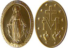 The image is of a small gold medallion with religious symbols carved on it.