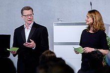 A man and a woman moderate a talk on a stage together.