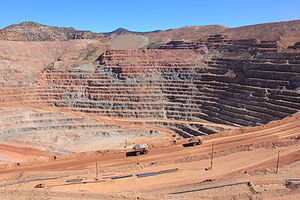 Porphyry copper deposit - Morenci mine open pit in 2012.  The red rocks in the upper benches, and the outcrops in the background, are in the leached capping. It appears that the bottom of the pit is in the mixed oxide-sulfide zone, and that's also what the two haul trucks in the foreground are carrying. Click to enlarge photo.