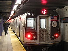 The end of a subway train with a red E on the end sits next to a platform with a person walking away.