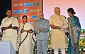 Narendra Modi presenting the Insurance Policies to the beneficiaries of the Social Security Schemes, at Nazrul Manch, in Kolkata. The Governor of West Bengal.jpg