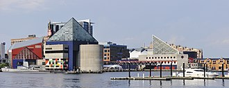 National Aquarium (Baltimore) - Left to right: The red building with a green glass front (north) wall holds the 2005 extension, the blue building with the glass pyramid top is the main building of poured concrete construction from 1981, and behind it,  across a pedestrian bridge to the east is the Pier 4 marine mammal pavilion.