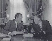 Two middle-aged men at a desk, in a forced pose of engaged conversation