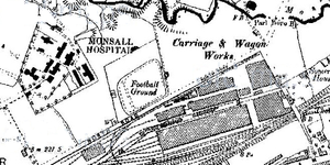 "Map showing a four-sided ""Football Ground"". The sides face diagonally, are slightly rounded, and are surrounded by ""North Road"" (in all capitals) and a railyard to the southeast, ""Monsall Hospital"" (all capitals) to the west, and ""Carriage & Wagon Works"" to the northeast"