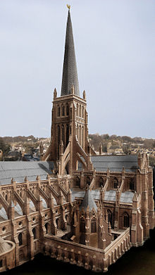 The central tower of a large gothic cathedral. The central tower is buttressed and with an imposing wooden spire. An octagonal chapter house is in the foreground.