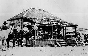 "Roy Bean - Roy Bean holding court in 1900, trying a horse thief. Bean is in the center of the photograph, sitting on a barrel and holding open his law book. The thief is sitting on a horse underneath the ""Ice Beer"" sign, with his hands behind his back."