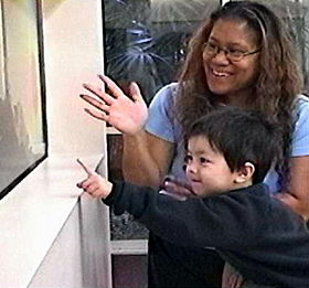 A young child points, in front of a woman who smiles and points in the same direction.