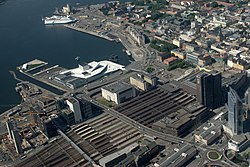 Aerial photo of Sentrum. The centre is located on the bottom-right side of the picture and the Waterfront with the Opera is located near the top. On the left side of the picture is Barcode. In the middle of the picture is the railway lines with the Oslo Central Station.