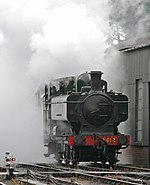 A green pannier tank locomotive appears from a cloud of its own steam and smoke.