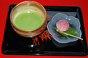 A bowl of matcha on a black lacquered tray with a traditional sweet