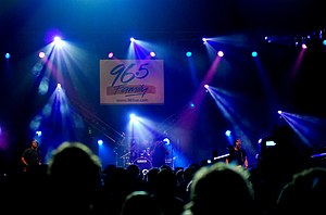 Project 86 performs at a concert. The entire band plays on a stage in front of a group of people, engulfed in blue lights.