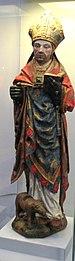 Раскрашенная статуя мужчины примерно 30 лет, одетого в золотую митру и священнические одежды красного, синего и золотого цветов.  В левой руке он держит Библию, а у его ног стоит животное, предположительно волк.