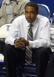 An African-American man sits with hands folded wearing a white shirt and tie