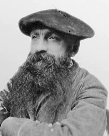 Photo of Rodin wearing a beret, looking into the distance.