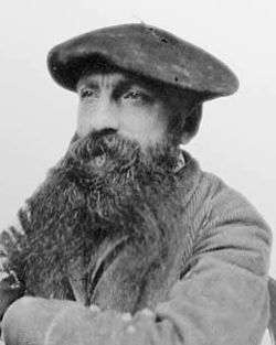 Photo of a bearded man wearing a beret, looking into the distance.