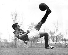 Photograph of a man striking a ball in mid-air