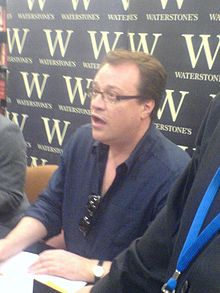 Davies in a navy-blue polo shirt, with one hand resting on a copy of his book.