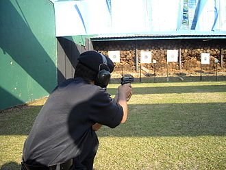 SIG Pro - An officer of the Royal Malaysia Police firing the SIG Sauer Pro 2022 with casing ejected out to the right side.