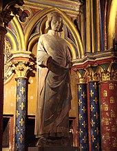 Statue de pierre peinte au milieu d'un décor gothique.
