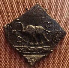 Eine quadratische Münze aus dunklem Metall, eine Ecke zeigt nach unten. Darauf ist ein Elefant mit erhobenem Rüssel dargestellt