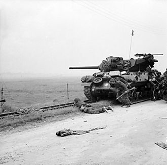 Northumberland Hussars - Troops take shelter near an M10 tank destroyer, used by 102nd (Northumberland Hussars) Anti-Tank Regiment; 6 June 1944