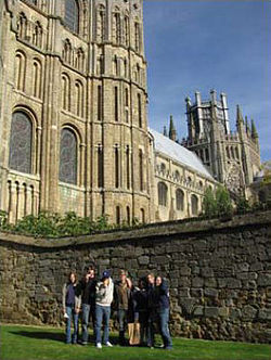 seven young people standing on grass in front of stone wall with Gothic building behind them