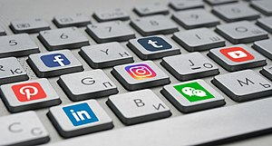 A keyboard with social media logos on the keys.