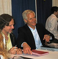 The image is of two men sitting at a table signing items. The one on the left is wearing a golden shirt and has brown hair and a mustache. The one on the right is looking up and has white hair.