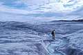 Standing by a Greenlandic melt water stream (7638364448).jpg