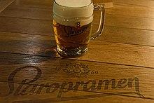 Une table en bois sur laquelle est posée une choppe de bière remplie de bière et de mousse; la marque Staropramen est écrite à même la table.