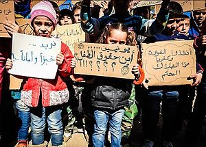 """2017 Aleppo suicide car bombing - Children holding placards with inscriptions """"We want bread and security"""", """"UNICEF where is children's rights?"""", """"save al-Fu'ah and Kafriya from certain death"""""""