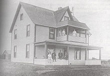 A three story house with four men and two children on the front porch and three women on the second floor balcony
