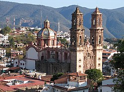 The façade of the church of Ss. Sebastian y Santa Prisca in Taxco) bristles with Mexican Churrigueresque ornamentation.