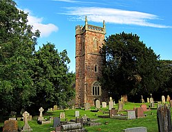 Stone building with arched windows and square tower, partially obscured by trees. Gravestones in the foreground