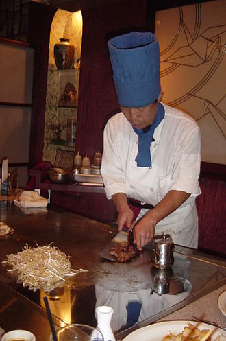 Hibachi - Teppanyaki chef cooks on a modern gas-powered griddle in a Japanese-themed steakhouse
