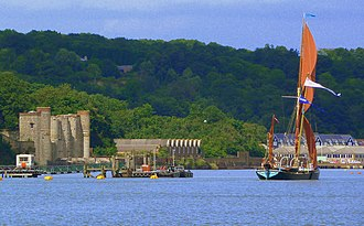 Upnor - A Thames Barge sails past the depot: Upnor Castle (left), 'B' Magazine (centre), No. 5 Shell Store (right).