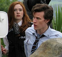 A woman with red hair wearing a policewoman's costume looks alarmed. In front of her, a dark-haired man in a tattered shirt and tie looks to the left.