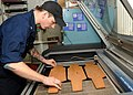 U.S. Navy Machinery Repairman 2nd Class Stephen M. Mills lines up award placards, known as skateboards, on a laser engraver in the engraving shop aboard the aircraft carrier USS Nimitz (CVN 68) 130117-N-BJ752-088.jpg